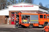 Feuerwehrmann am Loschfahrzeug vor der Feuerwehrwache