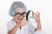 Girl chemist examines flask under a magnifying glass