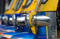 Detail of old tuk-tuk taxis with cracked paint in Bangkok. Shallow depth of field with parts of the nearest taxi in focus.