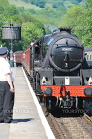 Steam train pulling into Grosmont station Yorkshire. Looking along platform towards a water tower poast a guard