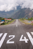 Small aircraft landing at the remote airfield at Lukla in the Nepalese Himalayas. Gateway to Mount Everest