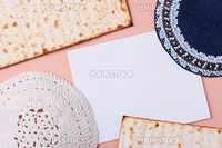 Blue and white kippahs laying next to matzah and a white piece of paper. Add your text to the paper.