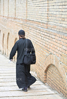 Young ortodox monk in black cassock against the brick monastery wall (the Kiev-Pecherskaya Lavra monastery, Kiev, Ukraine)