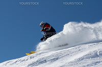 skier in clouds of snow powder against a blue sky