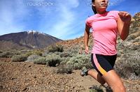 Running. Woman Cross country trail runner running on the mountain / volcano Teide on Tenerife. Beautiful mixed chinese asian / caucasian female model.