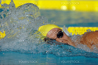 A freestyle swimmer with cap and goggles during a race.