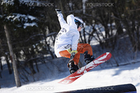 a snowboarder gets air as he jumps off of a rail in a snowboard competition