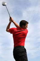 Young golfer with a driver against a blue clouded sky