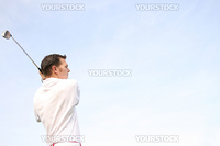 Young golfer in white against a pale blue skyFollow Through of a young professional golfer whilst practising on the range