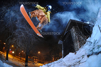 Jumping snowboarder in the city at night in winter