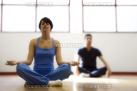 health club: man and women doing yoga. Dreamy atmosphere and shallow focus on her face