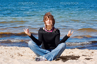 Young girl meditating at the beach