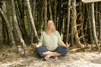 A pretty blond woman meditates in a bamboo grove.