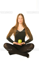 The portrait of a woman in lotus pose with a green apple in her hands