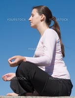 Meditation. The girl meditates with sky at background.