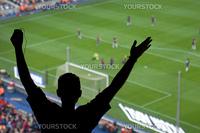 A soccer fan cheering for a goal in Spain