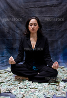 Rich woman meditating while sitting in money isolated on a dark background