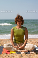 girl meditating on the sea coast sitting  in yoga asana padmasana