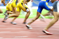 Image of 100 meters athletes in action with intentional blurring.