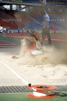Image of a long jumper in action with a measuring tape in the foreground.
