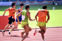 A blind athlete competing in a Men's 100 meters race. The blind athlete is seen here running in tandem with his guide.