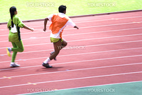A blind athlete competing in a Women's 100 meters race. The blind athlete is seen here running with her guide.