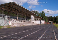 The small stadium with stands and benches for spectators, running tracks are visible with rubber coating