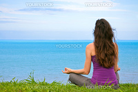 A beautiful young woman sitting meditating with a view of the ocean