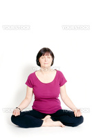 Aged woman sitting in lotus seat practicing yoga.