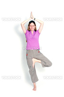 Young woman practicing yoga in the tree posture with closed eyes