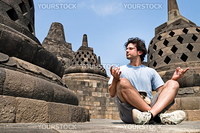 Young man meditating in a buddhist temple