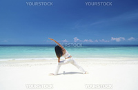 Woman practicing Yoga (Warrior Position) on the beach.