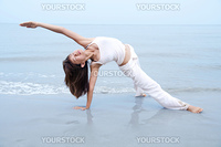 Woman practising Yoga(Gate Pose) on the beach.