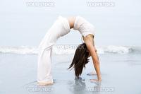 Woman practising Bridge Position Yoga on the beach.