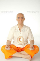 Man sitting in lotus position looking at camera, isolated on white