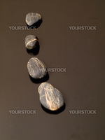 Curvy row  of pebbles on black reflective surface