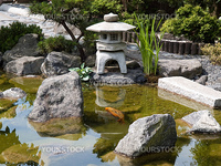 Details of Japanese garden with water pond and stone pagoda
