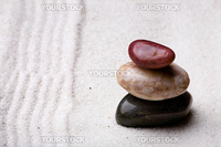 A stack of rocks in a zen rock garden with sand