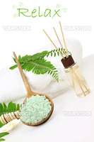 Green bath salts in a wooden spoon with essential oils and white towel. Extreme shallow DOF with selective focus on bath salts. Room for your text.