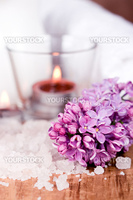 lilac, bath salt and candle closeup on wooden background