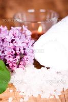 lilac, bath salt, towel and candle closeup on wooden background