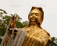 Kuan Yin the avartar of next Buddha statue in gold with pearl lace  from the servants in her hands, Korat, Thailand.