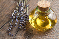 lavander oil with flowers on wooden table