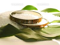 Two bracelets and bath salt on a green leaf