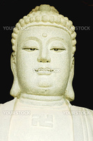 Ancient stone buddha statue on a black background