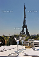 Luxury restaurant with Eiffel Tower behind in a blue sky