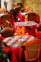 Set tables with tablecloth and glasses on restaurant outdoor patio