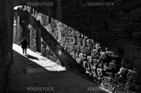 A pedestrian in a narrow medieval street in San Gimignano, Tuscany, Italy