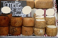 Aged french cheese wheels stacked on the marketplace