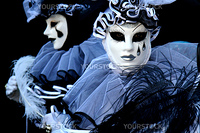 Two people dressed as Pierrot on black background, during the Venice Carnival